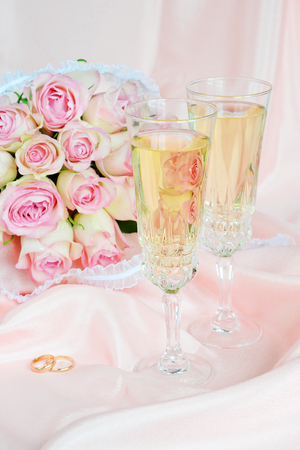 Bouquet of pink roses, wedding rings and two glasses of white wine on satin fabric background photo