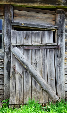 Rickety wooden closed door in an old house photo
