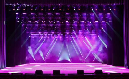 Verlichte lege concertpodium met rook en stralen van licht Stockfoto