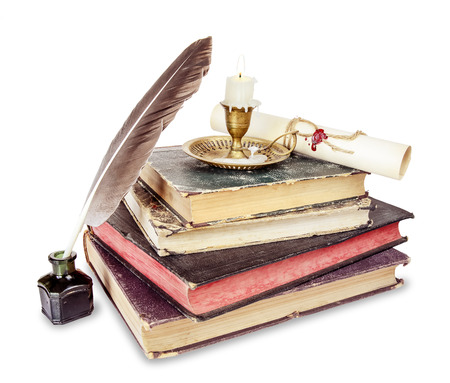 Old books, candle in candlestick, feather in inkpot and scroll with stamp Stock Photo