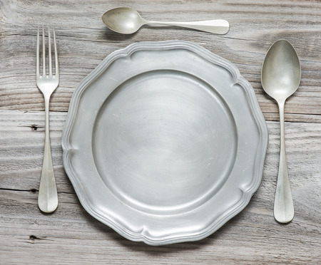 Vintage fork, spoons and pewter plate on old wooden boards