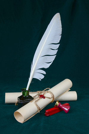 White feather in the inkwell, sealing wax, signet and two paper scroll on dark-green cloth