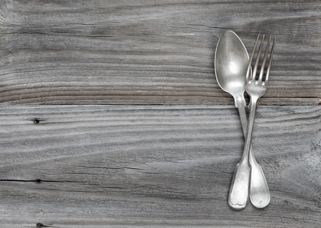 antique wood: Crossed vintage fork and spoon on old wooden boards Stock Photo