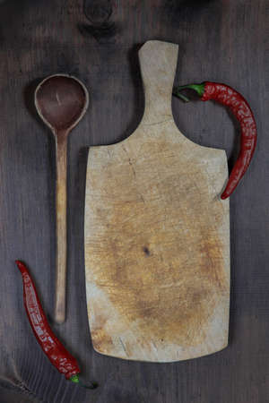 trencher: Vintage cutting board with red hot chili peppers and wooden spoon