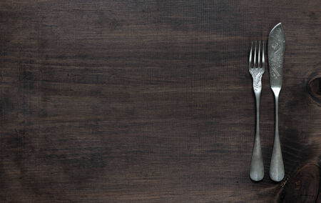 Vintage fork and knife for fish on old wooden board photo