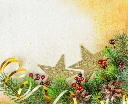 Christmas compositionon with fir branches and golden stars on a background of old paper photo
