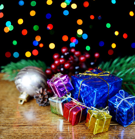 Gift boxes and spruce branches against a background of colored lights photo