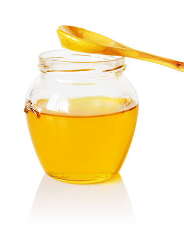 tidbit: Glass jar of golden honey with a wooden spoon