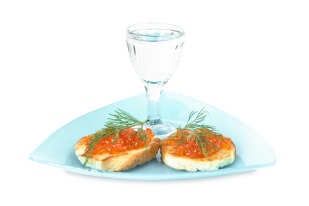 Two sandwiches with red caviar and glass of vodka on a blue triangular plate photo