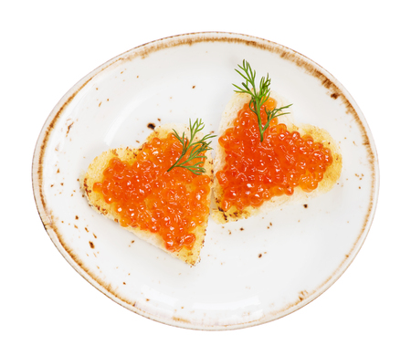 Two sandwiches heart shaped with red caviar on a porcelain plate photo