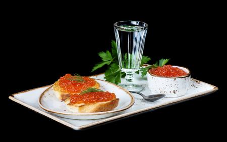 sandwiche: Panini con caviale rosso e un bicchiere di vodka su un piatto di porcellana isolato a nero