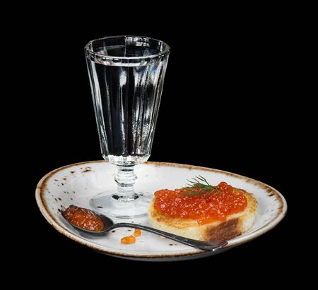 sandwiche: Sandwiche with red caviar and glass of vodka on a porcelain plate isolated at black