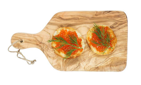 Two sandwiches with red caviar on the olive cutting board photo