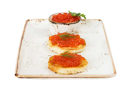sandwiche: Two sandwiches with red caviar on a porcelain plate