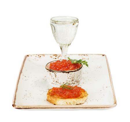 sandwiche: Sandwiche con caviale rosso e un bicchiere di vodka su un piatto di porcellana Archivio Fotografico