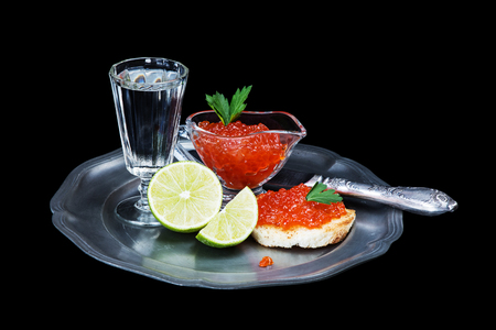 sandwiche: Sandwiche with red caviar, glass of vodka, sliced lime and old knife on a tin plate