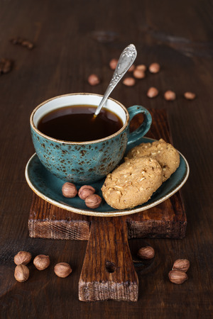 Black coffee in blue vintage cup on old dark cutting board photo