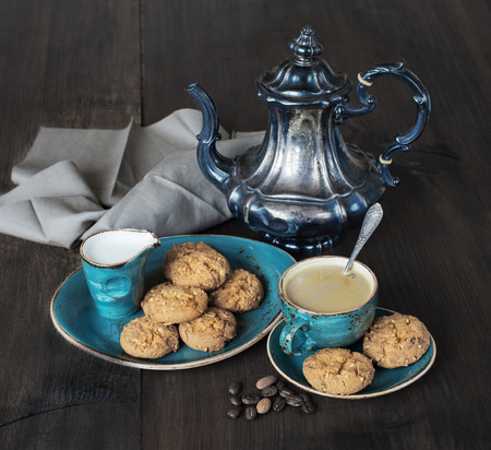 coffee pot: Coffee with cream in blue vintage cup, cookies and antique silver coffee pot on a old dark wooden boards