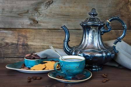 saucer: Black coffee in blue vintage cup, cookies, chocolate and antique silver coffee pot on a old dark wooden boards