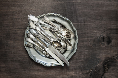 silver cutlery: Antique silver cutlery on vintage tin plate on old wooden background