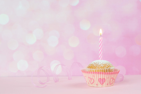 Small cupcakes with a one burning striped candle on a pink background Standard-Bild