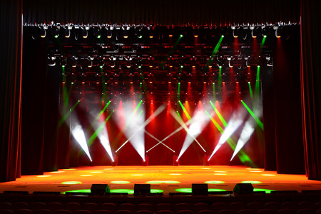 Illuminated empty concert stage with smoke and red and green beams