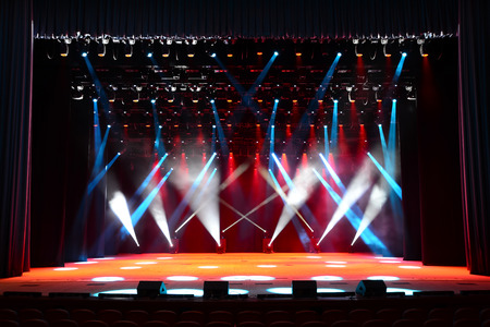 Illuminated empty concert stage with smoke and red, white and blue beams