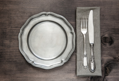Antique silver cutlery and vintage tin plate on old wooden background