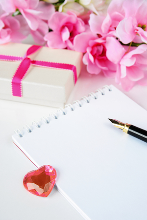 glass heart: Romantic still life with gift box, a notepad, old pen, pink flowers and a glass heart Stock Photo