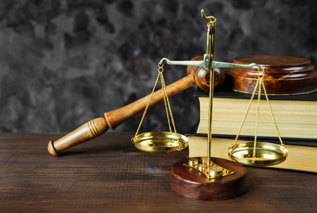 Symbolen van de wet: houten hamer, soundblock, schalen en twee dikke oude boeken Stockfoto
