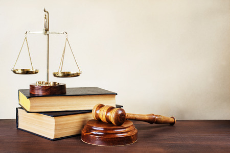 Symbols of law: wood gavel, soundblock, scales and two thick old books Archivio Fotografico