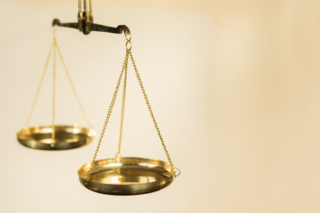 balanza en equilibrio: Dos cuencos de escalas de metal de oro en suspensión en las cadenas sobre un fondo beige