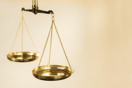 gerechtigkeit: Zwei Schüsseln mit Waage der goldenen Metall an Ketten aufgehängt auf einem beige Hintergrund Lizenzfreie Bilder