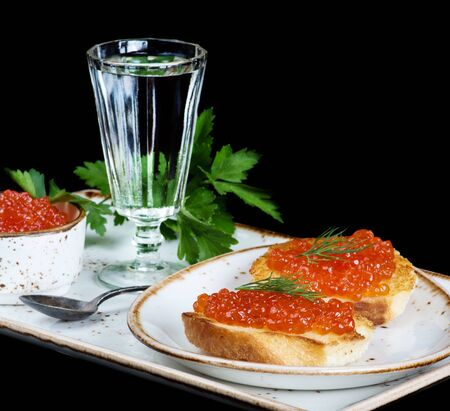 sandwiche: Sandwiches with red caviar and glass of vodka on a porcelain plate isolated at black