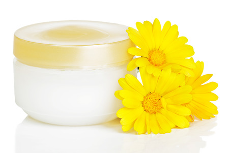 liniment: Closed jar of cream and three orange calendula flowers isolated on a white background