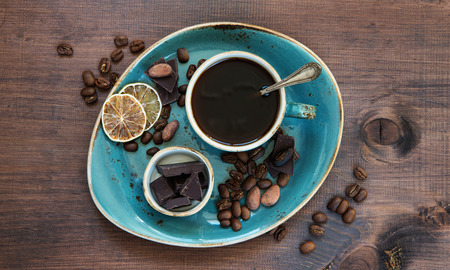 chocolate background: Black coffee in blue vintage cup and chocolate on a old dark wooden boards
