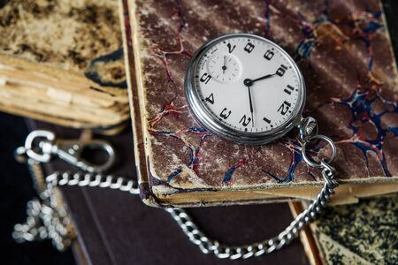 recollections: Vintage pocket watch with a steel chain lie on a pile of old books
