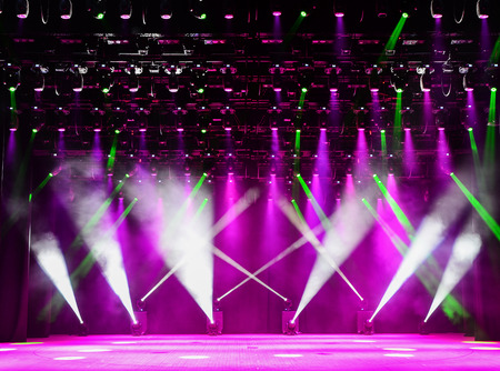 Illuminated empty theater stage with fog and green and magenta rays of light