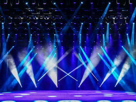Illuminated empty theater stage with fog and blue rays of light