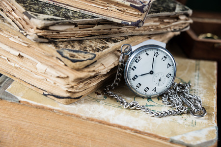 pocketwatch: Vintage pocketwatch with a steel chain lie on a pile of old books