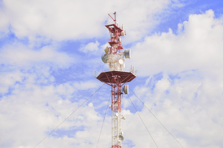 transmitting: Transmitting antenna against a blue sky with white clouds Stock Photo