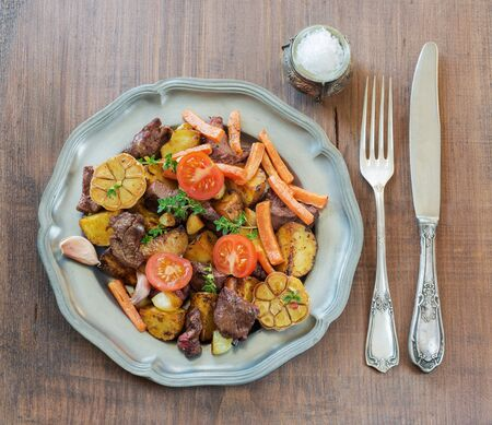 pewter: Roast venison with vegetables on a vintage pewter plates and old cutlery on a wooden table