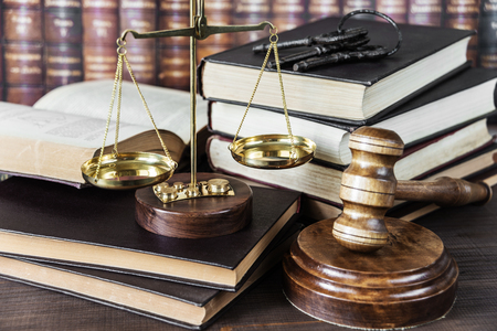 business crime: Wood gavel, bunch of keys, scales and stack of old books against the background of a row of antique books bound in leather