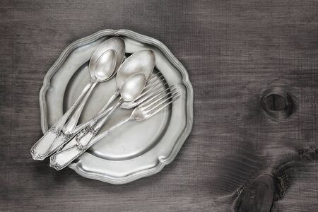 Antique silver cutlery on vintage tin plate on old wooden background