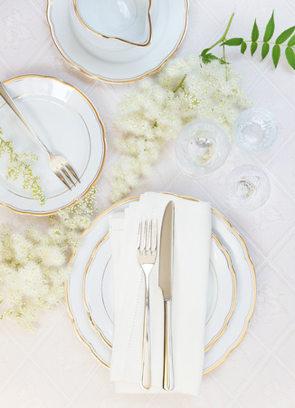 wedding: Top view of the beautifully decorated table with white plates, crystal glasses, linen napkin, cutlery and flowers on luxurious tablecloths Stock Photo