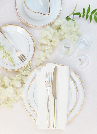 boda: Vista desde arriba de la mesa bellamente decorado con placas de color blanco, copas de cristal, servilleta de lino, cuberter�a y flores en manteles de lujo