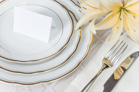 Beautifully decorated table with white plates, crystal glasses, linen napkin, cutlery and flowers on luxurious tablecloths, with guest card Archivio Fotografico