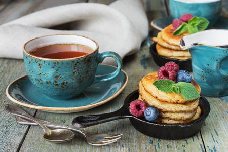 breakfast: El desayuno de panqueques, bayas frescas y té negro en estilo rústico Foto de archivo