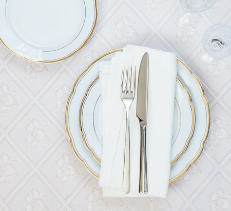 Top view of the beautifully decorated table with white plates, crystal glasses, linen napkin  and cutlery on luxurious tablecloths