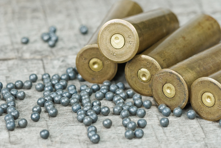 plumbum: Hunting cartridges and lead shot  on the background of old wooden boards